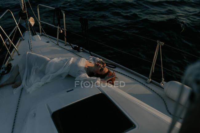 Розслаблена красива жінка лежить на носі корабля і відпочиває під час морської подорожі з закритими очима. — стокове фото