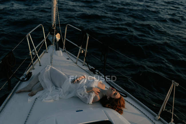 Relaxed beautiful woman lying on bow of ship and resting while enjoying sea trip with closed eyes — Stock Photo
