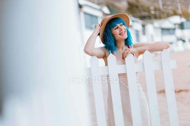 Romantic happy woman with dyed blue hair in sunhat and dress resting while leaning in fence at rural coastal town — Stock Photo