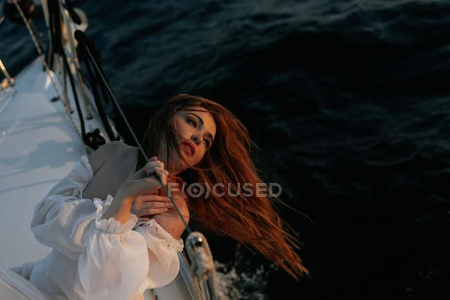 Femme tranquille en robe blanche de luxe, allongée sur un yacht pendant la croisière, regardant loin — Photo de stock