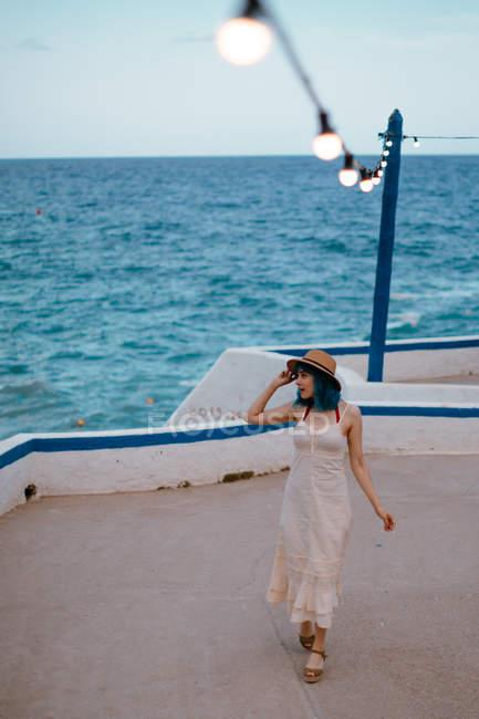 Вдохновленная женщина с синими волосами в шляпе и раздевалке прогуливалась вдоль бетонной пристани у разноцветного моря — стоковое фото