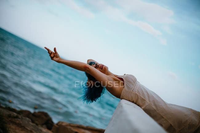 Side view of sensual carefree woman leaning on pier with back and stretching hand to waterfront — Stock Photo