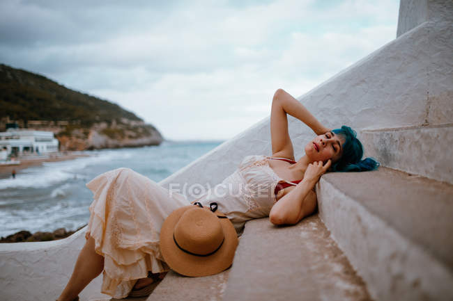 Side view of dreamy woman with colorful blue hair in sundress lying on stone steps on seaside — Stock Photo