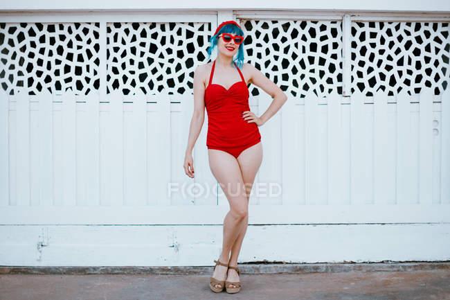 Модная женщина в ярких солнцезащитных очках с синей прической в красном купальнике, стоящая с протянутой рукой рядом с дизайнерской стеной — стоковое фото