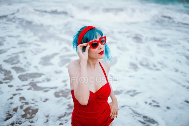 Femme à la mode avec des cheveux bleus en maillot de bain rouge brillant touchant lunettes de soleil rouges dans l'eau mousseuse — Photo de stock