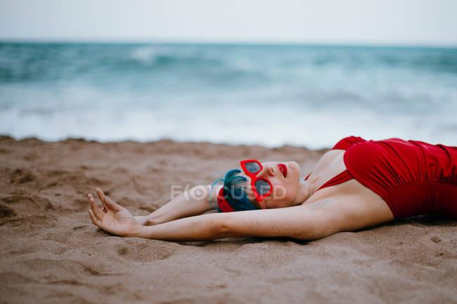 Femme à la mode avec des cheveux bleus en maillot de bain lumineux rouge profitant couché sur la plage de sable avec les mains tendues — Photo de stock