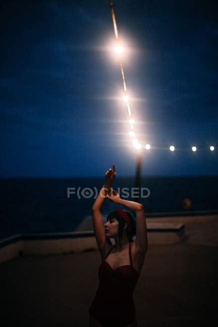 Calm woman in red vintage swimsuit moving with hand up under dark cloudy sky and bright spotlight — стокове фото