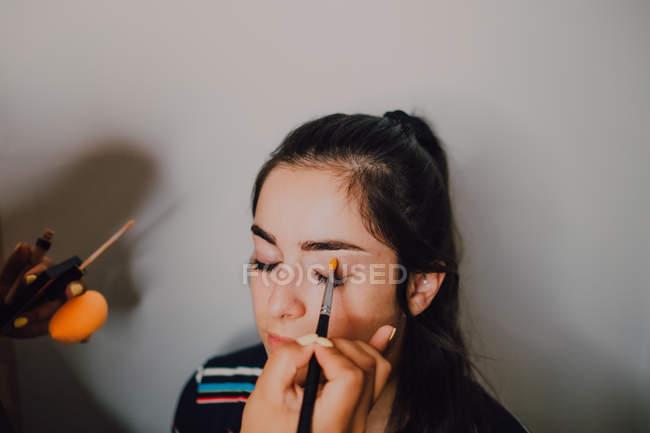Молодая женщина делает макияж профессиональным косметологом в салоне — стоковое фото