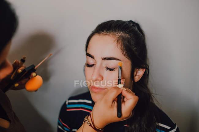 Професійна косметична працівниця в салоні приваблює молоду жінку. — стокове фото