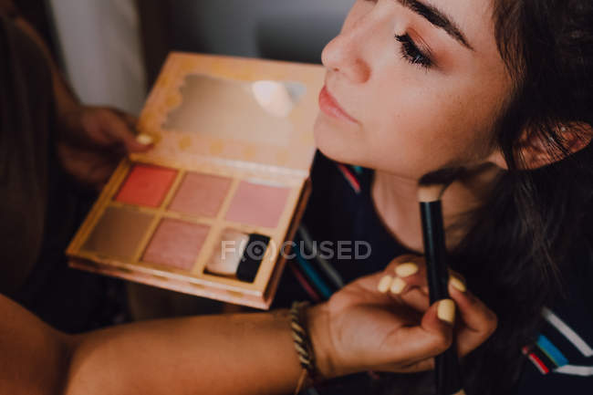 Beautiful young woman getting makeover by professional makeup artist in salon — Stock Photo