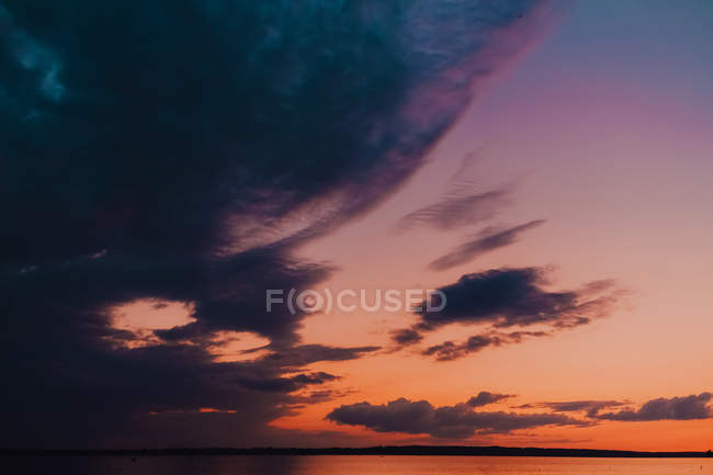 Stunning colorful sundown in warm summer evening reflecting lightly in sea surface — Stock Photo