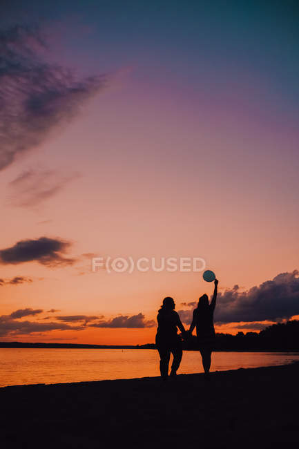Back view of anonymous women with balloon holding hands and walking along seashore during beautiful sundown — Photo de stock