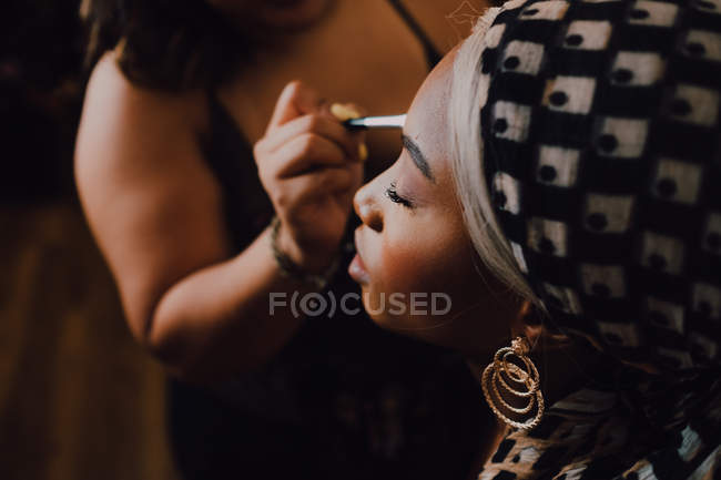 Attractive Black adult female applying eye shadow from professional makeup artist in studio — Stock Photo