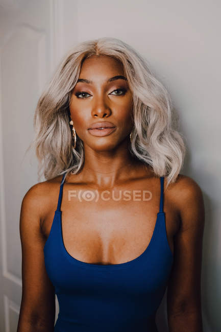 Portrait of adult African American woman with blond hair wearing blue and looking at camera — Stock Photo