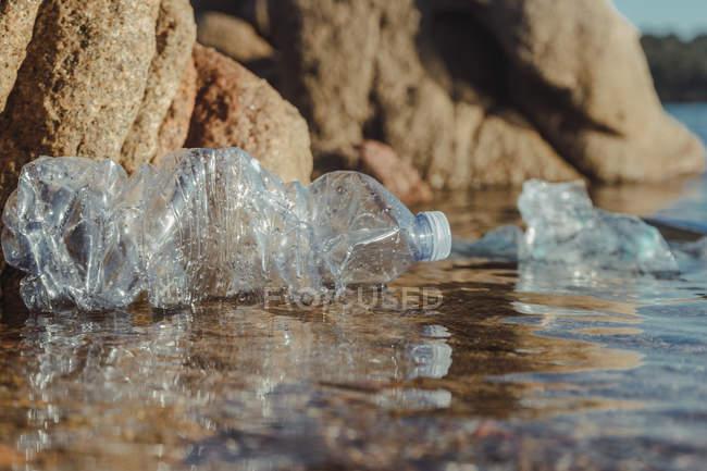 Botellas vacías de plástico arrugado residuos que yacen en agua clara en la playa cerca de las rocas - foto de stock