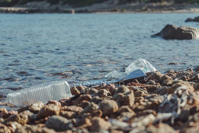 Botellas vacías de plástico arrugadas residuos que yacen en la roca junto al mar cerca del agua clara - foto de stock