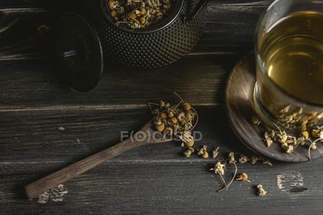 De dessus de marguerite séchée dans cuillère sur table en bois sombre près de tasse avec tisane — Photo de stock