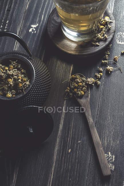 De arriba de la margarita seca en la cuchara a la mesa oscura de madera cerca de la taza con el té de hierbas - foto de stock