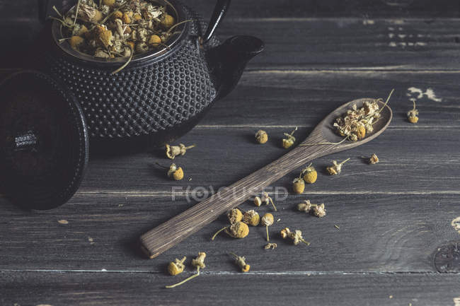 Tas de marguerite séchée dans une cuillère en bois sur la table noire pour la fabrication du thé — Photo de stock