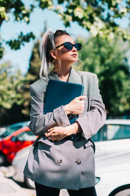 Empresária com óculos de sol penteado na moda e terno segurando laptop e olhando para longe no estacionamento no dia brilhante — Fotografia de Stock
