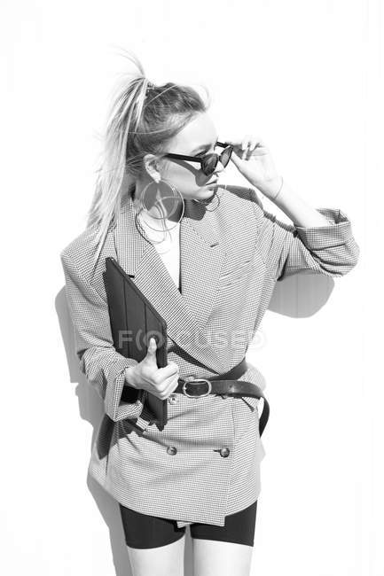 Businesswoman with trendy hairstyle, sunglasses and suit holding laptop and looking away on wall — Stock Photo