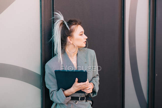 Businesswoman with trendy hairstyle and suit holding laptop and looking away on wall — Fotografia de Stock
