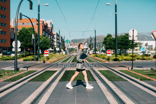 Side view of trendy woman in stylish suit with black notebook fast crossing road, looking around — Photo de stock