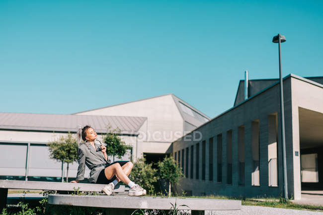 Trendy businesswoman working outside, sitting on round decorative panel plates nearby building — Stock Photo