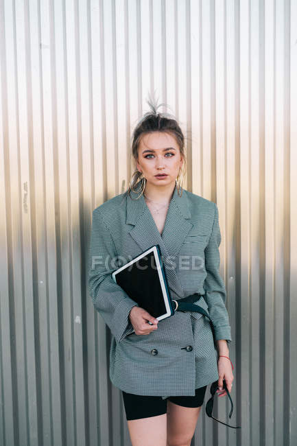Trendy businesswoman holding tablet and sunglasses, leaning on metal wall and looking at camera with questioning expression — Stockfoto
