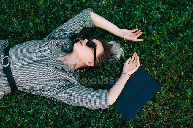 Top view of trendy businesswoman resting, raising hands and lying on green grass with laptop — Stock Photo