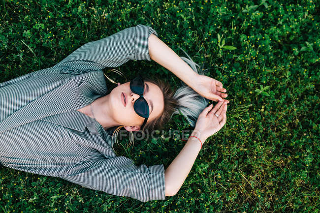 Top view of trendy businesswoman resting, raising hands and lying on green grass — Stock Photo
