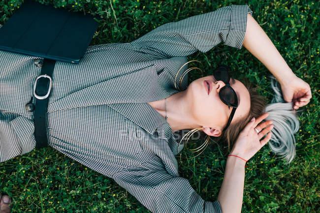 Vue de dessus de femme d'affaires à la mode se reposant, levant les mains et couché sur l'herbe verte avec ordinateur portable — Photo de stock