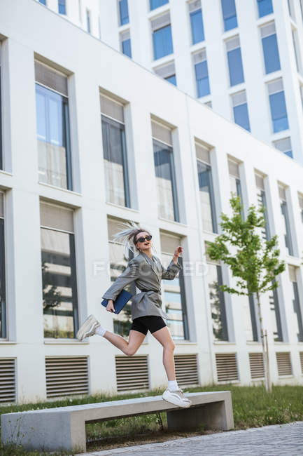 Trendy businesswoman holding tablet and sunglasses, jumping on business area and looking away — Stock Photo