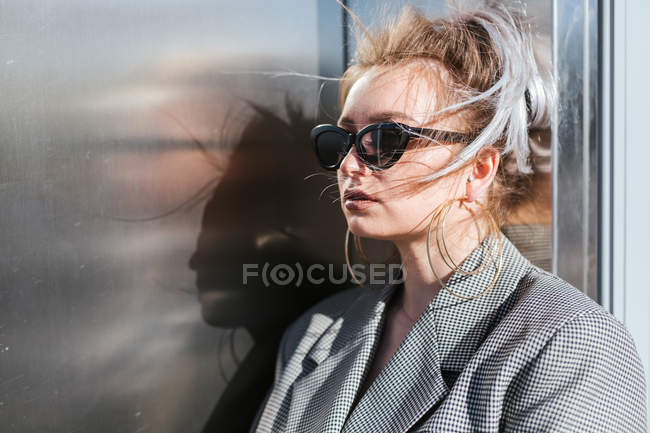 Fashionable attractive woman with trendy hairstyle and sunglasses nearby dark shiny metal wall looking away — Stock Photo