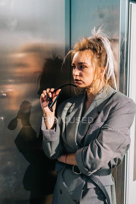 Модная привлекательная женщина с трепетной прической и солнцезащитными очками рядом с темной блестящей металлической стеной, отводящей вдаль взгляд — стоковое фото