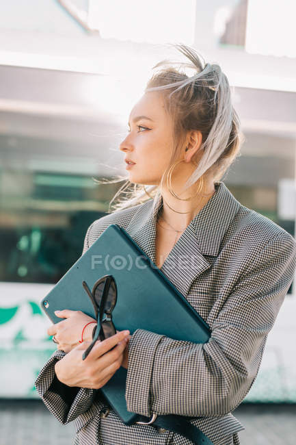 Seitenansicht einer stilvollen trendigen Geschäftsfrau, die auf den Zug wartet und gespannt auf den Bahnhof blickt — Stockfoto