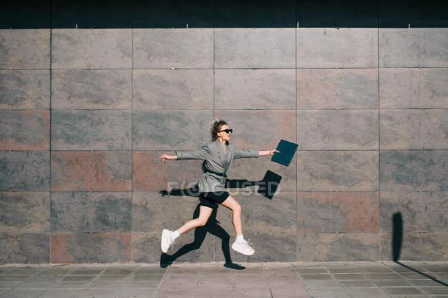 Seitenansicht einer stilvollen Geschäftsfrau, die entlang der Marmorwand springt und mit Tablet winkt — Stockfoto