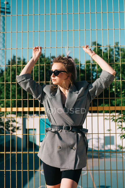 Trendy fashionable businesswoman looking away in sunglasses and leaning on yellow lattice in bright day on playground — Stock Photo