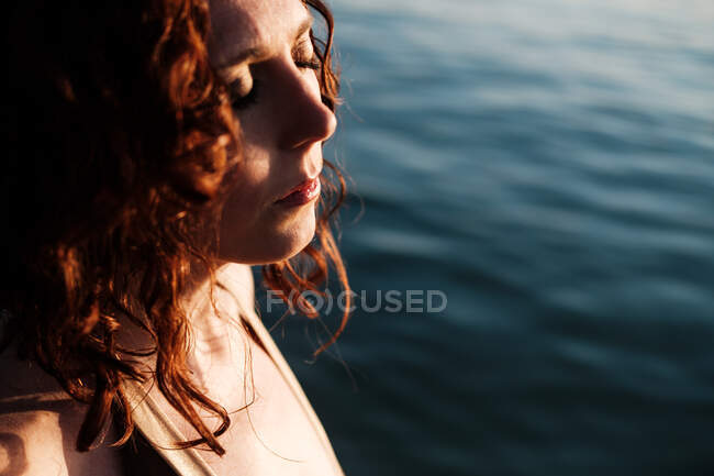 Vista lateral de la hermosa dama con los ojos cerrados de pie en agua de mar limpia en el día soleado - foto de stock