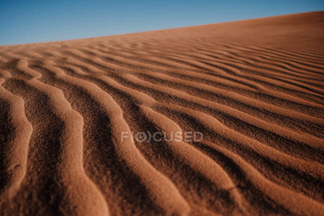 Closeup rippled sand surface on dune in arid desert against cloudless blue sky in Morocco — Stock Photo