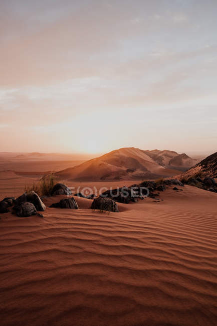 Cloudy sundown sky over hills and rocks in arid desert in evening in Morocco — Stock Photo