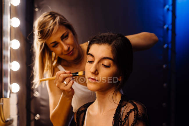 Side view of stylist applying makeup on brunette model sitting in front of illuminated mirror in dressing room — Stock Photo