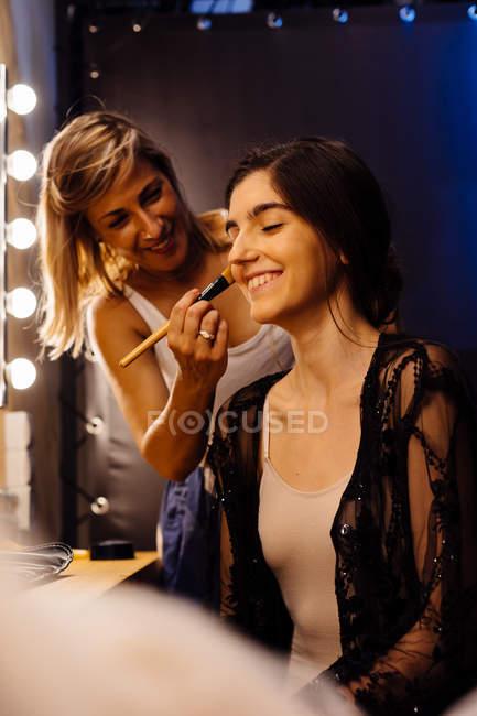 Vue latérale du styliste appliquant le maquillage sur le modèle brune assis devant un miroir éclairé dans le vestiaire — Photo de stock
