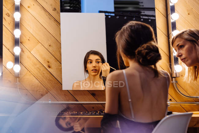 Back view of serious brunette woman applying red lipstick while doing makeup in dressing room with assistant — Stock Photo