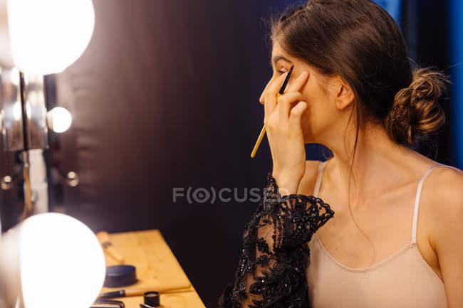 Vista laterale della donna attraente con i capelli scuri in abito nero trasparente facendo il trucco mentre seduto davanti allo specchio illuminato — Foto stock