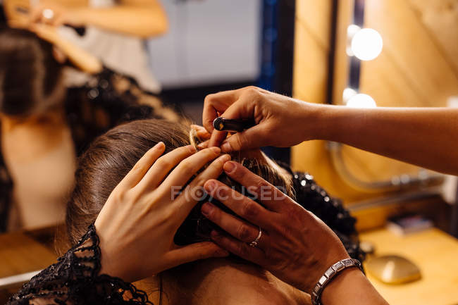 Back view of brunette woman fixing hair by crop stylist standing behind and reflecting in mirror in dressing room — Stock Photo