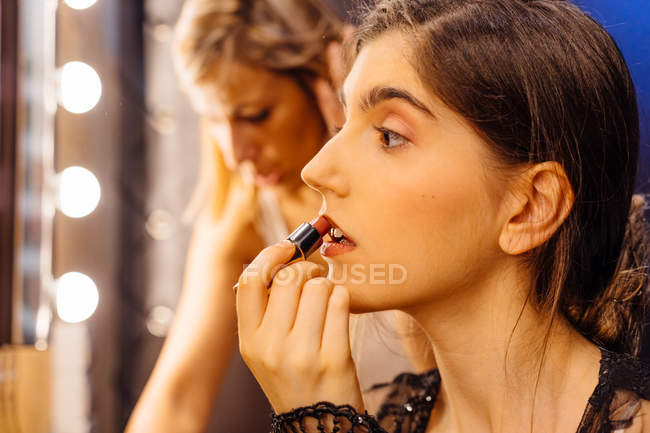 Side view of serious brunette woman in lace black dress applying red lipstick while doing makeup in dressing room — Stock Photo