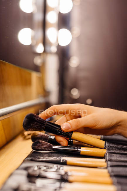 Cropped image of woman holding brushes near tools for professional makeup arranged on wooden table on blurred background — Stock Photo