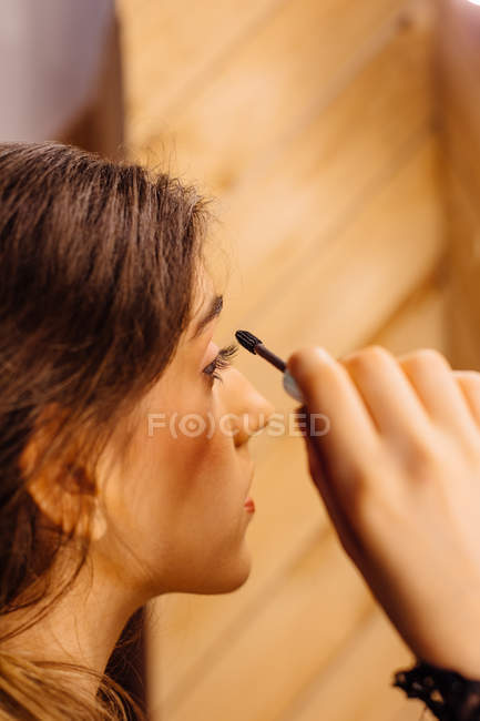 Side view of crop brunette attractive woman looking in mirror doing makeup applying mascara on eyelashes — Stock Photo