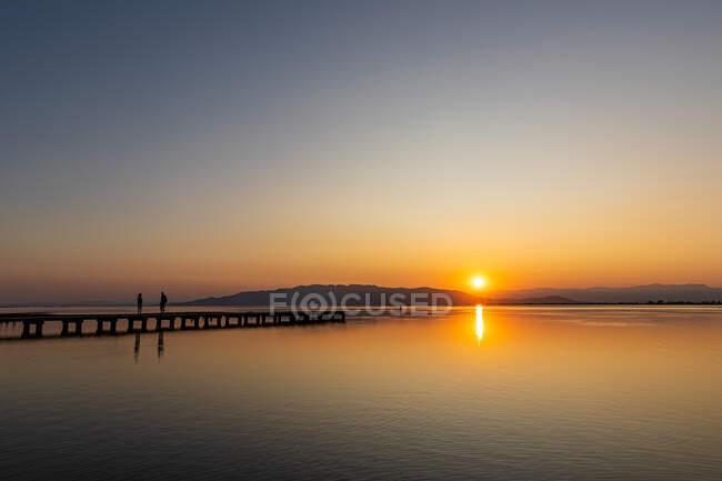 Cena romântica de um casal ao pôr-do-sol. Cores intensas de um pôr do sol com reflexos na água — Fotografia de Stock